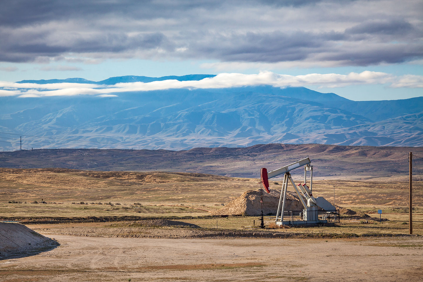 oil pump in large open dry plain of land with mountain in background and clouds above peregrine energy partners